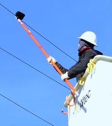 Line Worker Using A Voltage Detector Meter